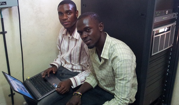Two PiliPili FM engineers, Salim Shatry and Ebrahim Abaker, viewing the AUI of the Nautel VS2.5 transmitter (installed right) on their laptop at the Mombasa transmitter site.