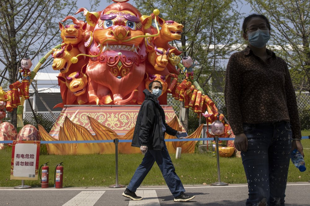 Residents wearing masks against the coronavirus walk past lantern sculptures at a park in Wuhan in central China's Hubei province on Thursday, April 9, 2020.